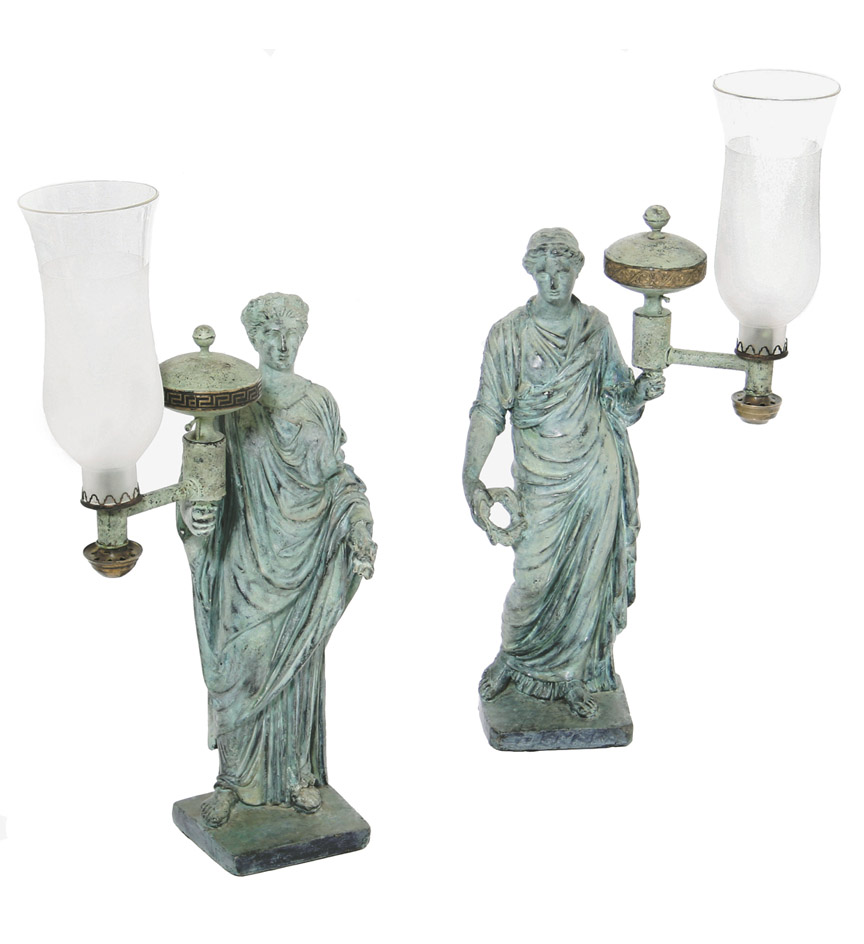 A pair of Regency verdigris-decorated figural lamps by Shout, each depicting a vestal virgin carrying a colza oil lamp with a circular reservoir and later glass shade, on rectangular plinths. Now wired. Signed 'SHOUT/HOLBORN'.  The fashion for lighting rooms with figurative lamps in plaster, bronzed in the Roman manner, proliferated from the end of the 18th century.  Most notable among the firms producing such figures were Robert Shout, Humphrey Hopper, Francis Hardenberg and James Deville.  The signature on these pieces relates to Garrard's Act of 1798, which was passed to protect individual makers and dictated that all subsequent works must be signed and dated.