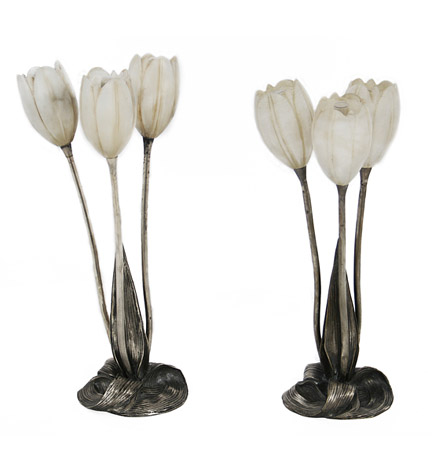 A pair of French silvered bronze tulip-form lamps by Albert Cheuret, the shades of alabaster, descending by way of stems to a base of interlaced leaves. One circa 1920, the other a later casting.
