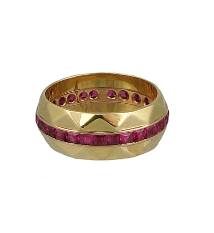A gold faceted wedding band inset with calibre rubies in 14k